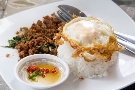 Thai food hot and spicy stir-fried pork with basil and fried egg photo