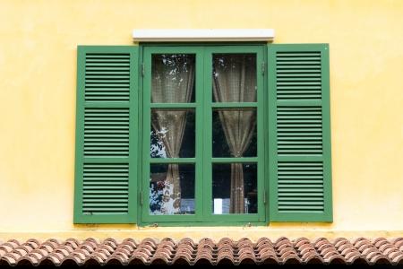 黄色の壁に緑の木製窓