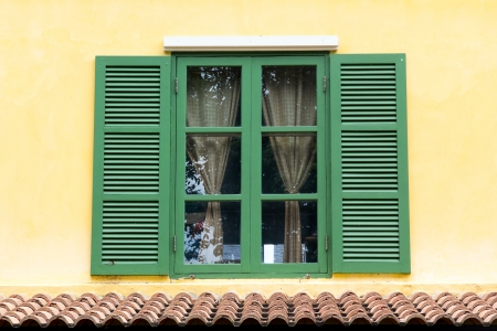 Green wooden window on the yellow wall Stock Photo