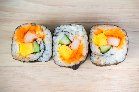 A roll of Maki Sushi on wood background-Japanese food photo