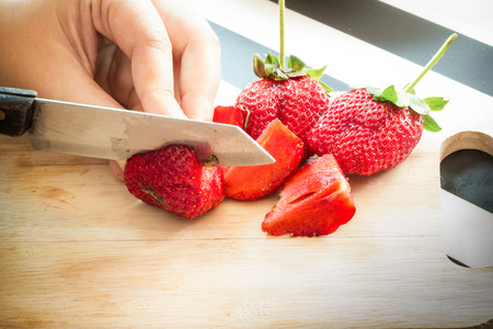 Hand chopping a fresh strawberry in kitchen photo
