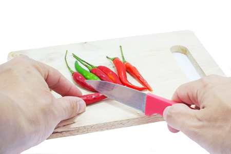 Hand cutting the red chilli by Knife on a wooden chopping board photo
