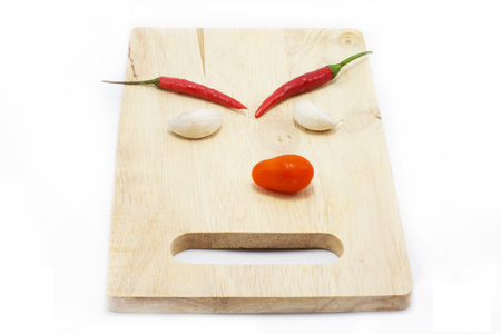 Funny chillis and garlic on a wooden chopping board