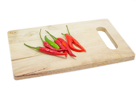 Red chili on wooden chopping board on white photo
