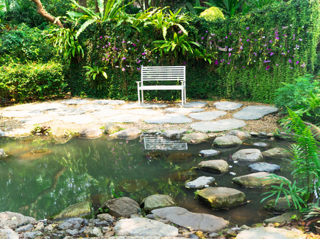 locating: White bench locating among the garden and small pond