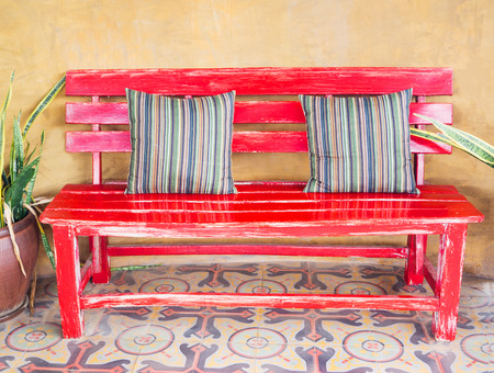 timber bench seat: Vintage red wood bench decorating in garden Stock Photo