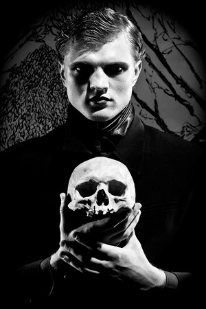 holding the head: A young man dressed in black with a skull in his hands. Black and white. Artistic created by me