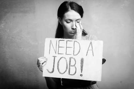 young girl holds a cardboard sign. Need a Job. black and white Stock Photo