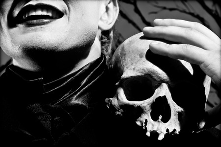 death head holding: A young man dressed in black with a skull in his hands. Black and white.