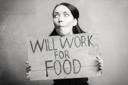 workless: young girl holds a cardboard sign. Will Work for Food. black and white.
