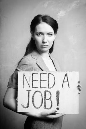 workless: young girl holds a cardboard sign. Need a Job. black and white Stock Photo