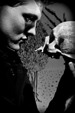 A young man dressed in black with a skull in his hands. Black and white. Artistic created by me