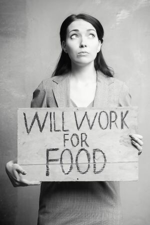 young girl holds a cardboard sign. Will Work for Food. black and white.