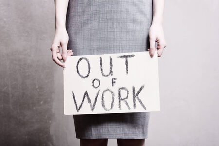 workless: young girl holds a cardboard sign. Out of Work.