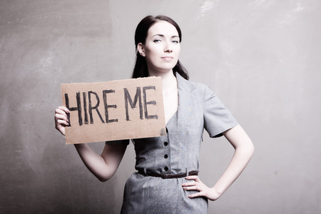 young girl holds a cardboard sign. Hire Me. Stock Photo