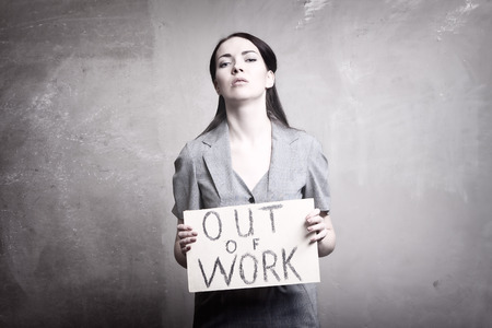 young girl holds a cardboard sign. Out of Work.