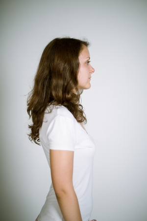 frizz: Portrait of a real young woman on a gray background in a white T-shirt. Shallow depth of field. Focus on the eyelashes.