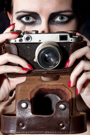 face make up: Camera in a leather case. The top half of the shot is occupied with eyes of the young beautiful girl with the vintage make-up Stock Photo
