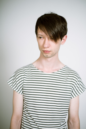 striped vest: Portrait of a real young man on a light background in a striped vest. Shallow depth of field. Focus on the eyelashes.