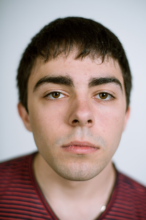 18 20: Portrait of a real young man on a gray background in a striped t-shirt. Shallow depth of field. Focus on the eyelashes