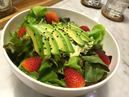 heathy: Closeup heathy avocado strawberry salad top with sesame with blur bokeh wooden tray and glass background