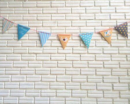 medium shot: Party pastel color flag strips on the white brick block wall (medium shot)