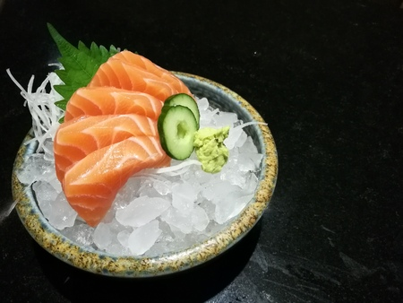 sever: Special Deluxe salmon sashimi set  on ice sever with wasabi and cucumber , traditional Japanese food with space, focus salmon with blur backgroup Stock Photo