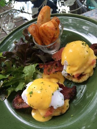 benedict: Eggs Benedict with smoked salmon top with fresh herbs and hollandaise sauce serve with green salad and French fries in green plate with blur background and mirror reflect, poached egg, top view