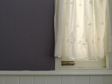 White Lace satin curtain hanging on window with sunlight semitransparent, vintage light purple wall and white siding decoration interior room, wall space Stock Photo