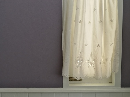 White Lace satin curtain hanging on window with sunlight semitransparent, vintage light purple wall decoration interior room