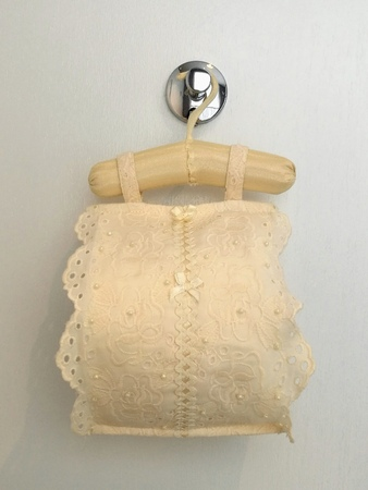Roll tissue cloth lace fabric cover with toilet paper roll for sanitary inside hanging on white background bathroom, closed up Stock Photo