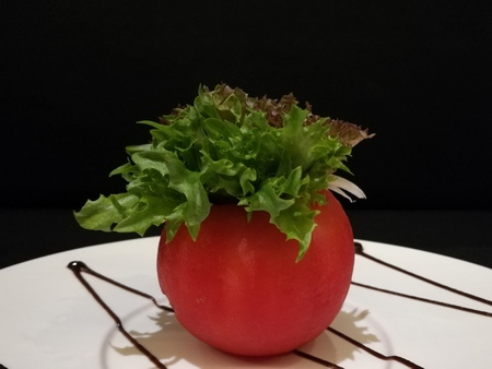 Healthy tomato salad stuff with lettuce and tuna, stylist food, fusion food, Close-up, black isolate background