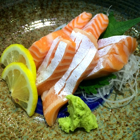 Special Deluxe salmon sashimi set  on ice sever with wasabi and cucumber, Maguro sashimi traditional Japanese food, closed up focus salmon with blur background Standard-Bild