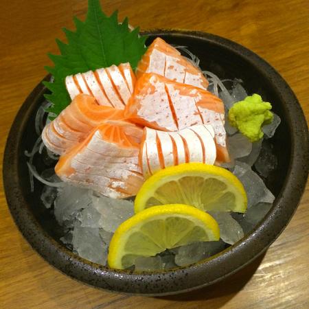 Der spezielle deluxe Lachssashimi, der auf Eis eingestellt wird, trennen mit Wasabikürke und Zitrone, traditionelles japanisches Lebensmittel Maguro-Sashimis, schloss herauf Fokuslachse mit Unschärfehintergrund Standard-Bild