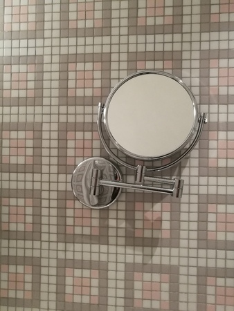 Mirror make up hanging on vintage marble tile  wall in toilet at home or hotel with blur bathroom wall background, Magnifying mirror, makeup mirror, household wares Stock Photo