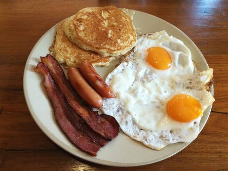 continental food: American Breakfast double fried egg, Bacon and sausages serve with butter pancake on white plate on wooden table, Homemade Continental breakfast at home kitchen, Hotel morning breakfast