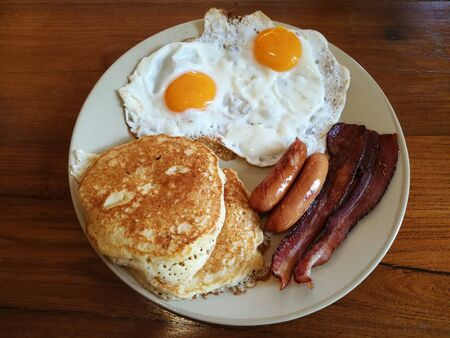 American Breakfast double fried egg,Bacon and sausages serve with butter pancake on white plate on wooden table, Homemade Continental breakfast at home kitchen, Hotel breakfast