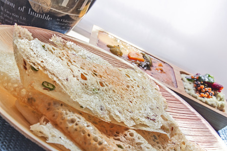 South Indian Rava Dosa along with coconut chutney and Sambhar made of Spices and lenthils, served on a traditional bamboo plate