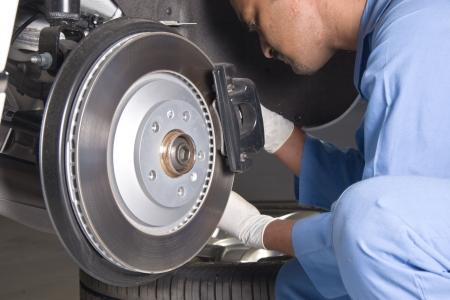 tire fitting: Auto mechanic checking brakes Stock Photo