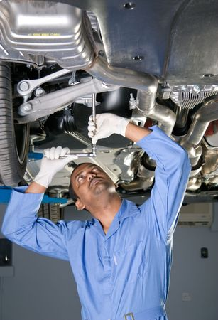 tire fitting: auto mechanic working under car on a lift