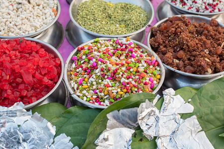 Different types of colorful garnish pan masala used to decorate betel leaf banarasi paan with selective focus