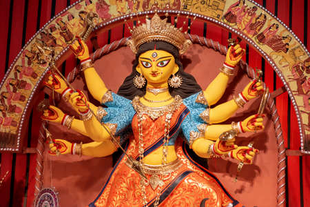 Goddess Durga idol at decorated Durga Puja pandal, shot at colored light, in Kolkata, West Bengal, India. Durga Puja is biggest religious festival of Hinduism and is now celebrated worldwide.