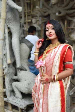 Portrait of a young and beautiful Indian woman in red and white traditional ethnic sari and gold jewellery in front of the clay idol of hindu goddess Durga. Indian culture, religion and fashion Stockfoto