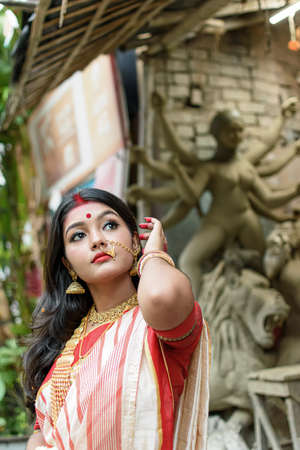 Portrait of beautiful Indian girl standing in front of Durga Idol wearing traditional Indian saree, gold jewellery, and bangles. Maa Durga agomoni shoot concept.