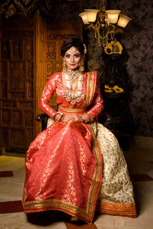 Magnificent young Indian bride in luxurious dress and precious jewellery is sitting in a chair in a luxury apartment. Classic vintage interior. Wedding fashion. Stock Photo