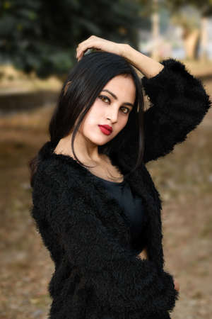 Portrait of very beautiful young attractive brunette Indian woman wearing black outfit posing fashionable in a blurred background. Lifestyle and Fashion.