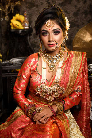 Stunning Indian bride in luxurious bridal costume with makeup and heavy jewellery is sitting in a chair in with classic vintage interior in studio lighting. Wedding lifestyle and fashion.