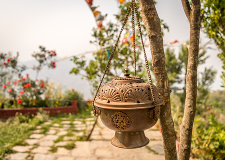 Metal Dhoop Batti Stand Hanging on a tree branch. This pot covered in a substance that is burned to produce a pleasant smell, especially as part of a religious ceremony. Stock Photo