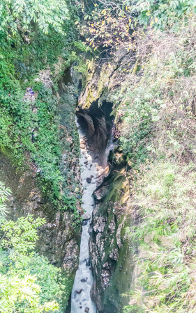 A Himalayan River Gorge in Kathmandu Nepal: A deep channel formed by a river that has eroded the earths crust over millions of years. This gorge is very large and visible from top.