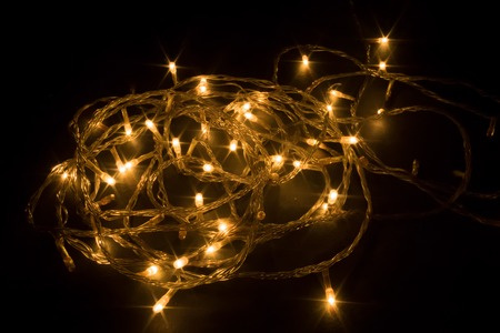 Diwali chain light, spiral shape, design to decorate street or home fireworks, dark black background shot in festival time or new years eve carnival, copy space. Remove darkness, decoration concept